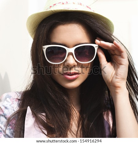 Young sexy brunette woman closeup portrait. Stylish woman posing on the street with interested look and green hat - stock photo