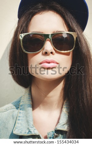 Young sexy brunette woman closeup portrait. Stylish woman posing with interested look and sunglasses and  cap on her head. - stock photo