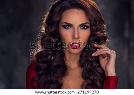 Young sexy brunette woman fashion portrait. Red lips and dress.