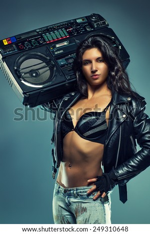 Young sexy brunette woman in black leather jacket, jeans and lingerie listening big old boom box. - stock photo