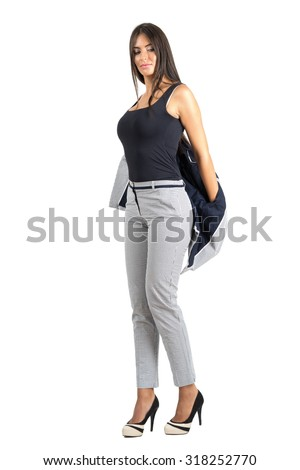 Young sexy business woman putting on suit jacket. Full body length portrait isolated over white studio background.