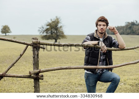young sexy country boy next to a wooden fence, standing outside in nature