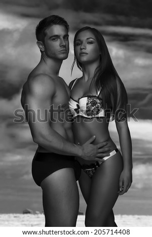 Young sexy couple in swimwear standing close to each other in black and white - stock photo