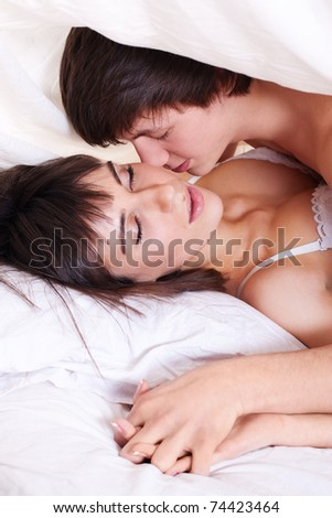 Young sexy couple making love in bed under the blanket - stock photo
