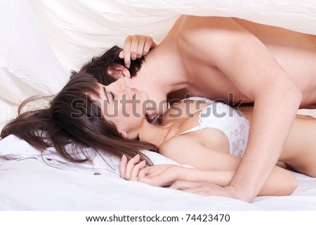 Young sexy couple making love in bed under the blanket
