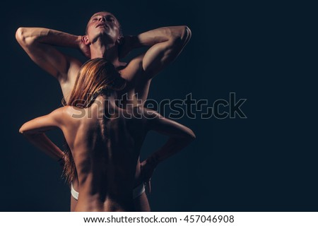 young sexy couple of pretty slim sporty woman with long hair and handsome muscular man with fit body and bare chest with torso in panties on studio background, copy space