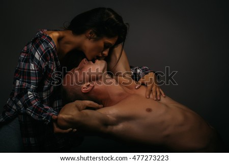 young sexy couple of pretty slim woman with long hair in checkered shirt embracing handsome naked man with muscular body in studio on grey background