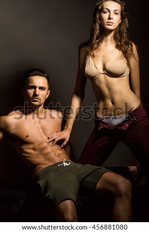 young sexy couple of pretty woman in beige bra with wet hair and handsome macho man with muscular torso and athletic body in studio on grey background