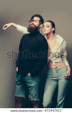 young sexy couple of woman with pretty face in stylish white shirt bra and pants near handsome bearded man with long beard in jeans shorts in studio on grey background