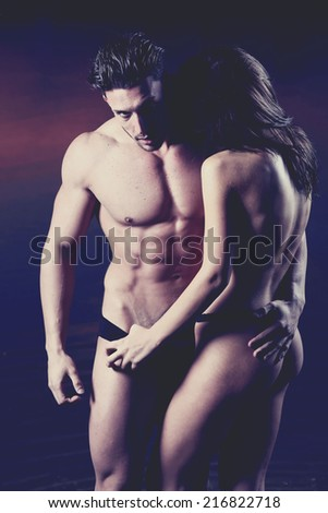 Young sexy couple on beach topless at sunset..Low light - stock photo