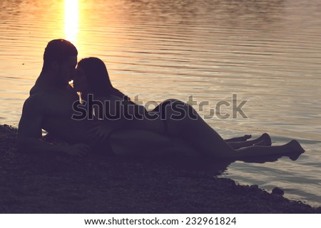 Young sexy couple on beach topless at sunset.Silhouette couple kissing over sunset background Fashion colors. - stock photo