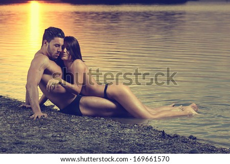 Young sexy couple on beach with sun rising in background .Fashion colors.  - stock photo
