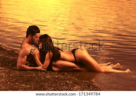 Young sexy couple on beach with sunset in background .Fashion colors.  - stock photo