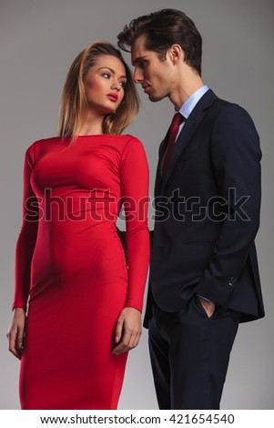 young sexy couple ready to kiss, elegant man in suit standing in the back of an attractive woman in red dress
