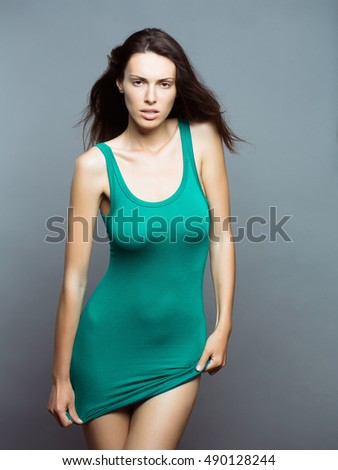 young sexy fashionable woman or girl with long brunette hair and pretty face in stylish green dress on slim body in studio on grey background