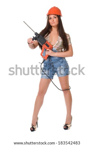 Young sexy female dressed in jeans and orange helmet holding hammer  electric drill. White isolated background.