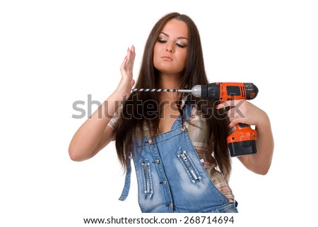 Young sexy female dressed in jeans  holding a cordless electric drill on a white isolated background