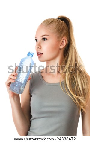 Young sexy fitness girl drink water from plastic bottle isolated over white background - stock photo