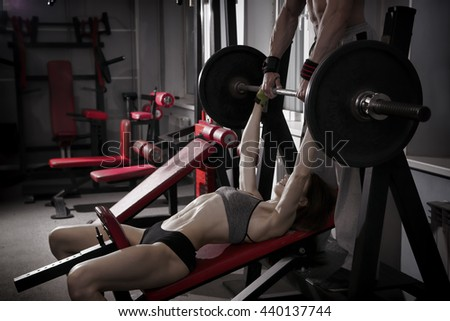 Young sexy fitness girl workout with barbell in the gym. Brunette woman in sport wear. Perfect muscular body. Toning image - stock photo