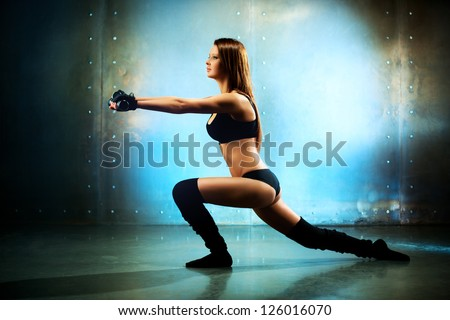 Young sexy fitness woman. On wall background.