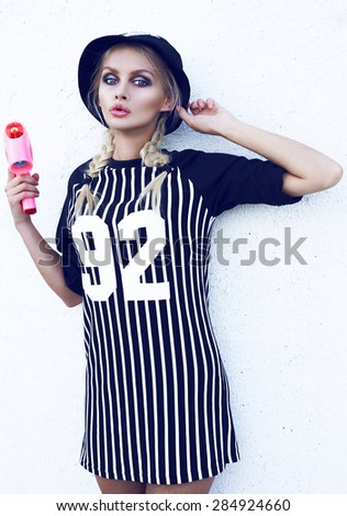 Young sexy girl.Fashion portrait of young beautiful woman in cap.Bright background.Outdoor lifestyle portrait.Swag style in fashionable clothes.Blond hair.Big blue eyes.Pink gun. - stock photo