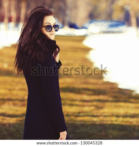 Young sexy girl in a nice fashionable coat and sunglasses middle ground