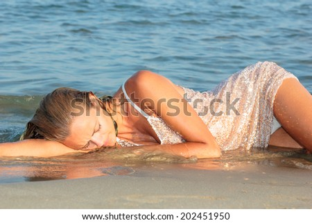 young sexy girl in bikini and wet shirt at the beach. Sensual attractive woman in water wearing bikini. Woman with perfect body relaxing on the beach. - stock photo