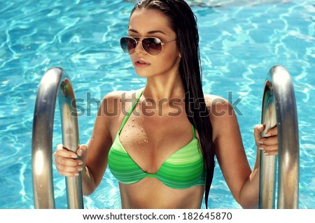Young sexy girl in green bikini going out of pool  - stock photo