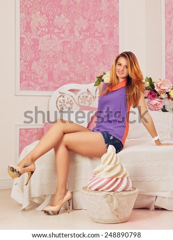 young sexy girl in pink bedroom with big cake - stock photo