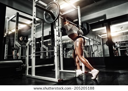 Young sexy girl in the gym doing squat with barbell - stock photo