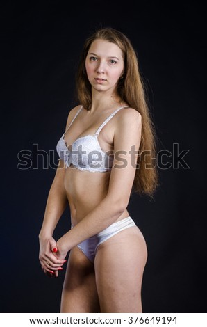 young sexy girl in white lingerie on a black background