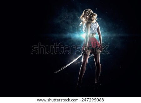 Young sexy girl is standing with the swords in th dark spotlight - stock photo