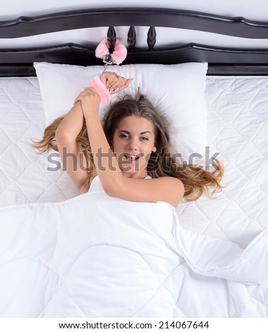 Young sexy girl lying in bed with handcuffs chained to a bed in her bedroom