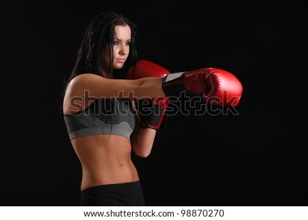 Young sexy girl over black background with boxing gloves - stock photo
