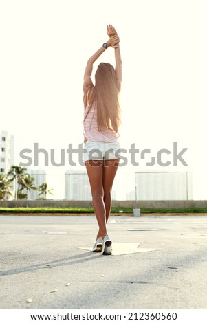 young sexy girl walking on the street dressed in trendy shorts and t-shirt - stock photo