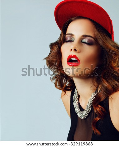 young sexy girl with parted lips, red lips and a red baseball cap with an expression of desire on his face, in the style of RnB - stock photo