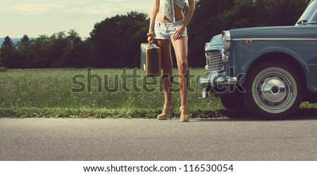 Young sexy girl with suitcase and vintage cars - stock photo
