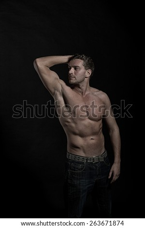 Young sexy handsome athletic man with naked torso on dark background, side view - stock photo