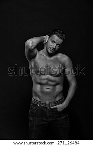 Young sexy handsome athletic man with naked torso on dark background with copyspace - stock photo