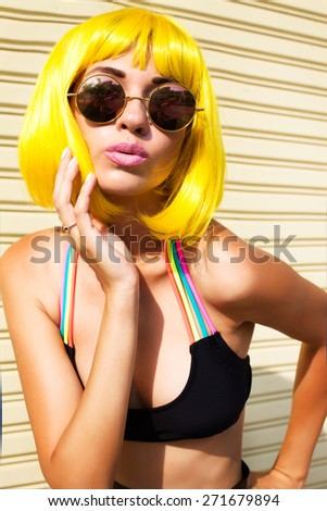 Young sexy happy woman looking at camera and  going crazy,punk and funky. Portrait of trendy girl having fun wear yellow wig and fashion sunglasses.posing on the white wall, not isolated.Fashion look - stock photo