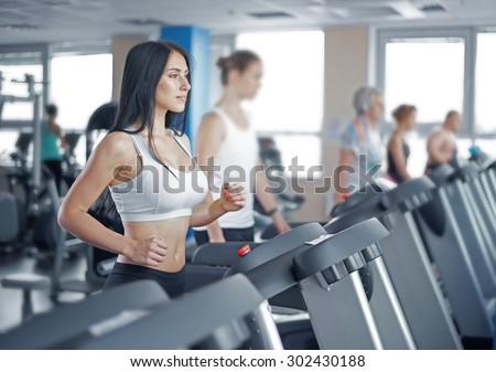 young sexy lady running on treadmill in gym - stock photo