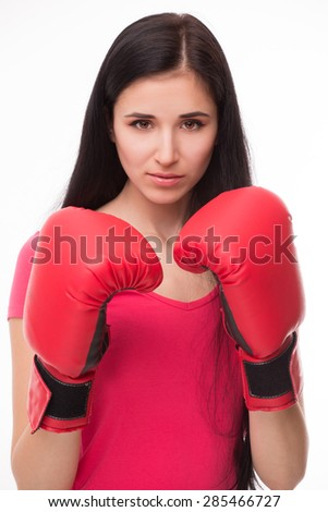 Young sexy looking like real boxer. Model in pink T-shirt with red-coloured boxing-gloves on posing for photographer.