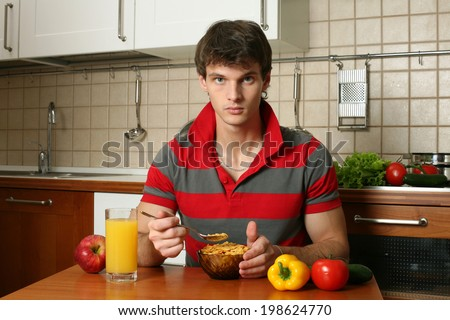 Young sexy man eating his breakfast at the kitchen - stock photo