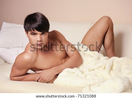 Young sexy man lying on a bed and looking at camera