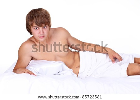 Young sexy man lying on white bed