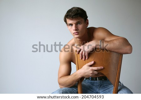 Young sexy man sitting on the chair