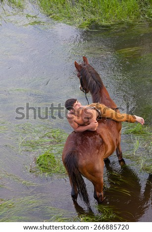 young sexy man with a naked torso lies on grain of the horse standing in the river - stock photo