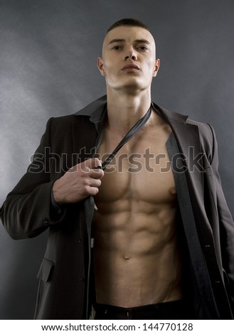 Young sexy man with athletic body posing on black background. - stock photo