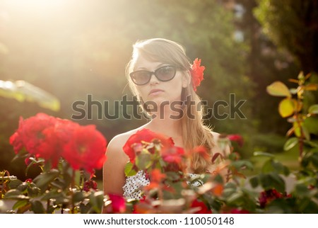 young sexy model in flower garden smelling red roses - stock photo