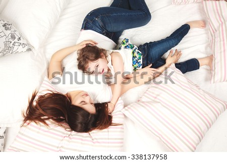 Young sexy mother and her little daughter lying in bed with pillows, smiling - stock photo